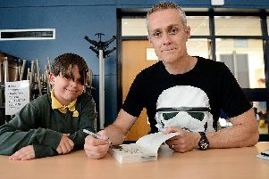 Bestselling children's author Dan Smith signs one of his books for Fens Primary School pupil Theo Ward.  Picture by FRANK REID