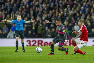 Referee Gavin Ward plays on as Pablo Hernandez has his shirt pulled by former Leeds United player Adam Clayton. Picture: Tony Johnson
