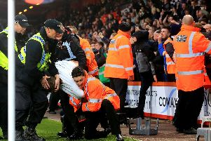 A Newcastle United fan is removed from the pitch by stewards and police at the end of the Premier League match at the Vitality Stadium, Bournemouth. Pic: Mark Kerton/PA Wire.