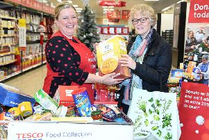 One of last year's volunteers helps a shopper donate to the Tesco Food Collection. (PHOTO BY: Andrew Parsons/i-Images)