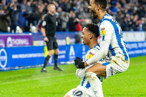 Chris Willock (kneeling) and Fraizer Campbell celebrate the latter's first Huddersfield Town goal