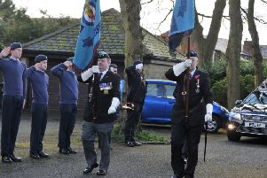 Standard bearers lead the funeral cortege for John Valentine as cadets look on.