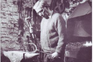 Robert Taylor blacksmith, making a horseshoe at Green Smithy, Mewith, near Bentham, in 1933. Robert is wearing leather gaiters to prevent hot iron sparks going down his boot tops.
