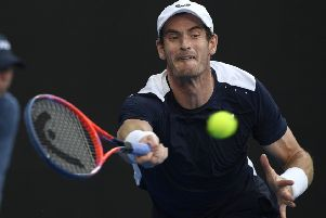 At full stretch: Britain's Andy Murray hits a forehand return in his first round match against Spain's Roberto Bautista Agut.
