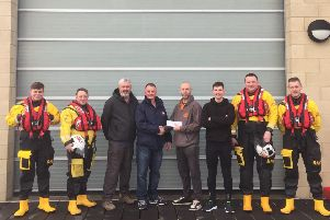Members of Surfwar Free Ride hand over a cheque to Blyth RNLI crew. Picture by Robin Palmer/RNLI