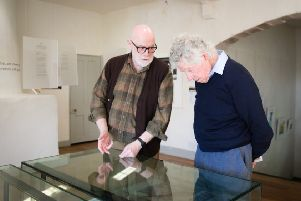 Poet Ian Duhig shows a visitor around the exhibition.