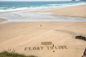 Aerial photos of the RNLI's Respect the Water Float to Live message sand art created by a sand artist at Perranporth beach, Cornwall.
