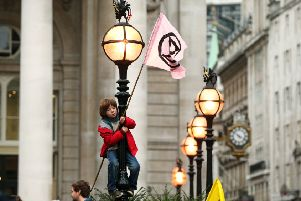 A young protester standing on a lamp post, in front of The Royal Exchange, London, during an Extinction Rebellion (XR) climate change protest. PA Photo. Picture date: Monday October 14, 2019. See PA story ENVIRONMENT Protests. Photo credit should read: Jonathan Brady/PA Wire