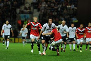 Preston striker Chris Beardsley is wrestled to the floor during the win against Huddersfield in 2012 - watched by Tom Clarke who was then with Huddersfield