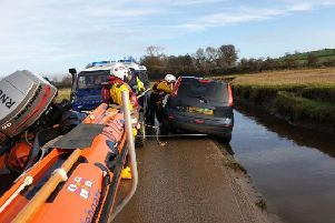 Lifeguards secure the vehicle after it slips off the causeway leading to Sunderland Point near Lancaster