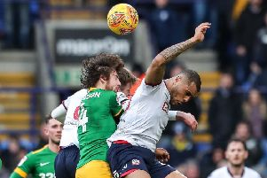 Preston midfielder challenges Bolton striker Josh Magennis in the air