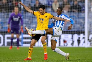Huddersfield Town's Terence Kongolo, right, challenges Wolverhampton Wanderers' Raul Jimenez on Tuesday night (Picture: Martin Rickett/PA Wire).