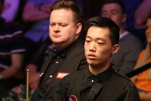 Record exit: Luo Honghao, right, falling to Shaun Murphy at The Crucible.