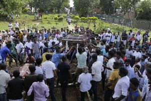 Sri Lankans prepare to bury the coffins carrying remains of Berington Joseph, left, and Burlington Bevon, who were killed in the Easter Sunday bombings in Colombo, Sri Lanka (AP Photo/Eranga Jayawardena)