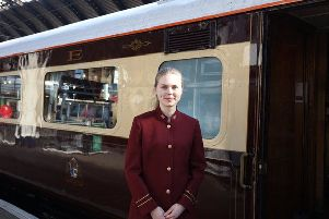A stewardess stands alongside the Northern Belle.
