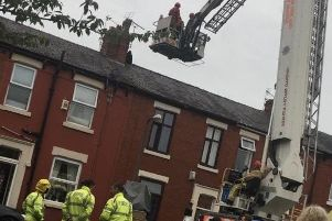A cherry-picker was used to help get the man down safely.