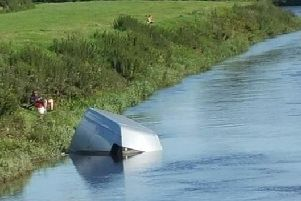 A local fisherman relaxes near the half-submerged Ford Transit in the River Ribble near London Road, Walton-le-Dale