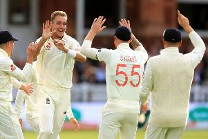 England's Stuart Broad and team-mates celebrate taking the wicket of Australia's David Warner at the end of day two of the Ashes Test match at Lord's.