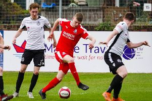 Action from Easter Monday's win for Brig (in red) at Marine (photo: Ruth Hornby)