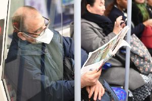 A man on an underground train wearing a protective mask