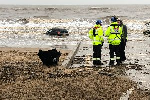 The car's owners made their way to safety with their dog, but were unable to free their car from the wet sand
