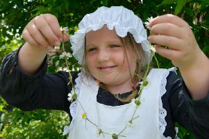 A girl making a daisy chain, an activity the National Trust thinks children should do by the age of 12