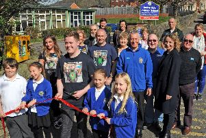 Joe Robinson cuts the ribbon at the newly-installed defibrilator at Darley Dale Primary School on Wednesday after a major fundraising drive by the community. Pictures by Anne Shelley.