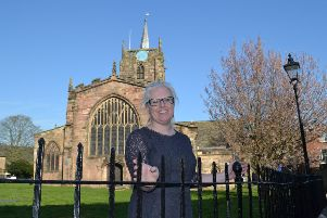 Helen Carrington, Derbyshire Dales District Council's parks and street scene officer, and the restored railings at St Mary's Church in Wirksworth.