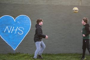Children play football in the park next to graffiti in support of the NHS. Photo:Justin Setterfield
