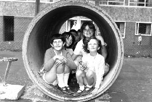 Youngsters shelter from a shower in the playground at Worsley Mesnes housing estate in 1969