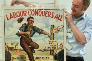 Archivist Alex Miller with one of the posters