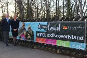 Coun Peter Jackson and Coun Cath Homer next to the advert at Morpeth Railway Station.