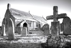 An atmospheric shot of a church and gravestones, by Jimmy Morse.