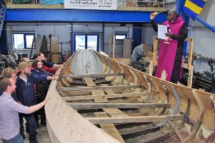 The Archbishop of York, Dr John Sentamu, blesses the coble built by Blyth Tall Ship Project trainees.