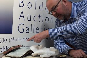 Gallery director Giles Hodges with accessories including a plaster cast of Alberts, face and hands, Henrys notebook, and photographs and documents.
