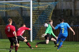Zack Dale chips the ball past Ben Morrow in the Litherland goal