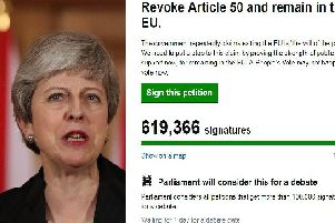 Theresa May is pictured with the petition.