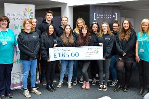 The hard working apprentices from Project Digital hand over a cheque to Pendleside Hospice for the cash they made from their enterprising business idea.