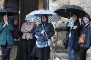 Tour de Yorkshire spectators try to keep dry outside the church ahead of the riders coming through Pocklington.