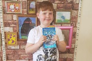 Vincent Brooke with the signed book he won for achieving the Gold Award in the Lancashire Reading Trail at Nelson Library. (s)