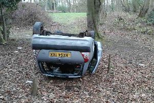 The car was dumped on its roof near woods
