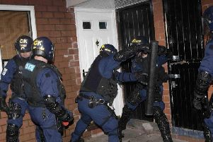 Officers using a battering ram to gain access to a property. (pic by WYP)