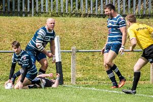 Joe Fox's crunching tackle allows Lewis Jackson to score one of his three tries for Featherstone Lions against Stanningley while Gaz Gale celebrates. Picture: Jonathan Buck