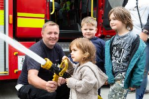 Fire fighter Mark Taylor, with Ivan Abbakumov, Matilda and Eddie Rosenthal, during the open day at Rastrick Fire Station