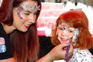 Five-year-old Phoebe Stephenson gets her face painted by Kether Barnett, proprietor of Cloud 9 Faces