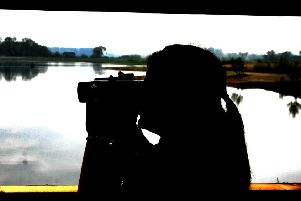 010519 Laura Harman from the  Yorkshire Wildlife Trust looking across the Riveside Lagoon from a bird hide  at the new  Ripon City Wetlands nature reserve.