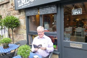 Harrogate BID chairman John Fox leafs through the ha ndy new guide outside independent Harrogate cafe LMDC.