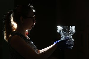 Vicky Price, British Museum's  assistant collection manager, with a piece by glassmaker Tapio Wirkkala from Nordic by Nature at Weston Park Museum