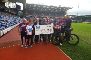 Burnley cyclists hand over cheque to Barry Kilby following their sponsored bike ride