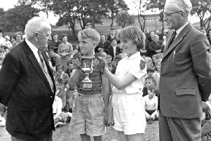 Mr T A Gedling, former headmaster of Cleadon Park Junior School, South Shields, presents the A J Wares Cup to the captains of Red House, the winning house at the school's sports day.  Looking on is headmaster, M P Ward.